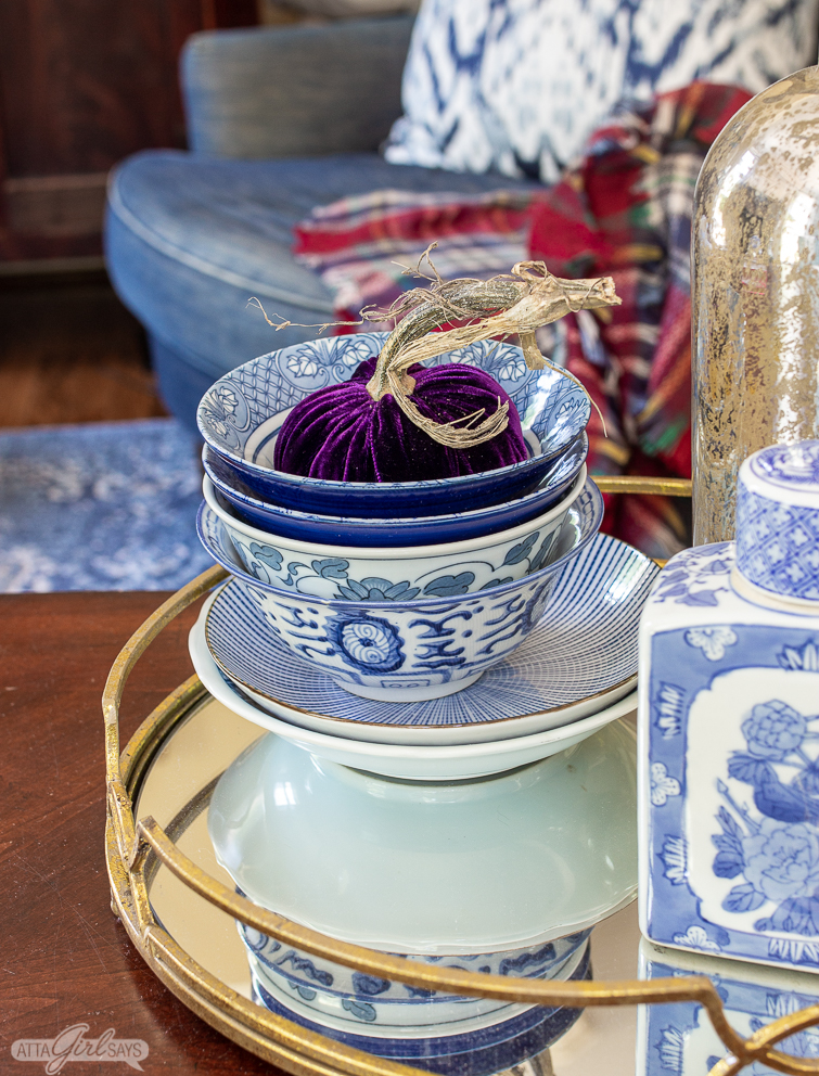 purple velvet pumpkin in a stack of blue and white bowls on a mirrored tray