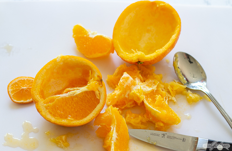 Scooping out the orange fruit to create a bowl out of the peel