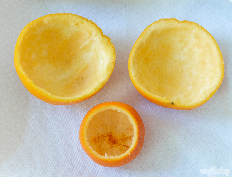Two empty orange rinds and a hollowed out mandarin orange rind