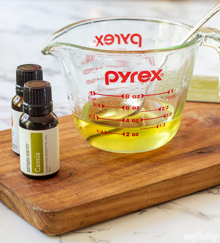 measuring cup of melted wax beside two bottles of essential oils
