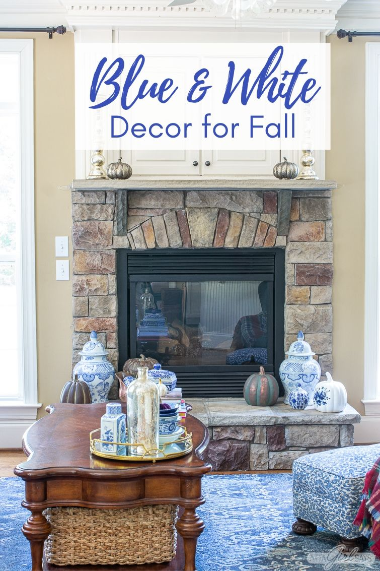 store fireplace with a TV cabinet over it decorated for fall with blue and white chinoiserie and copper pumpkins