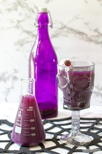purple Halloween pumch in a glass beaker and a skull goblet