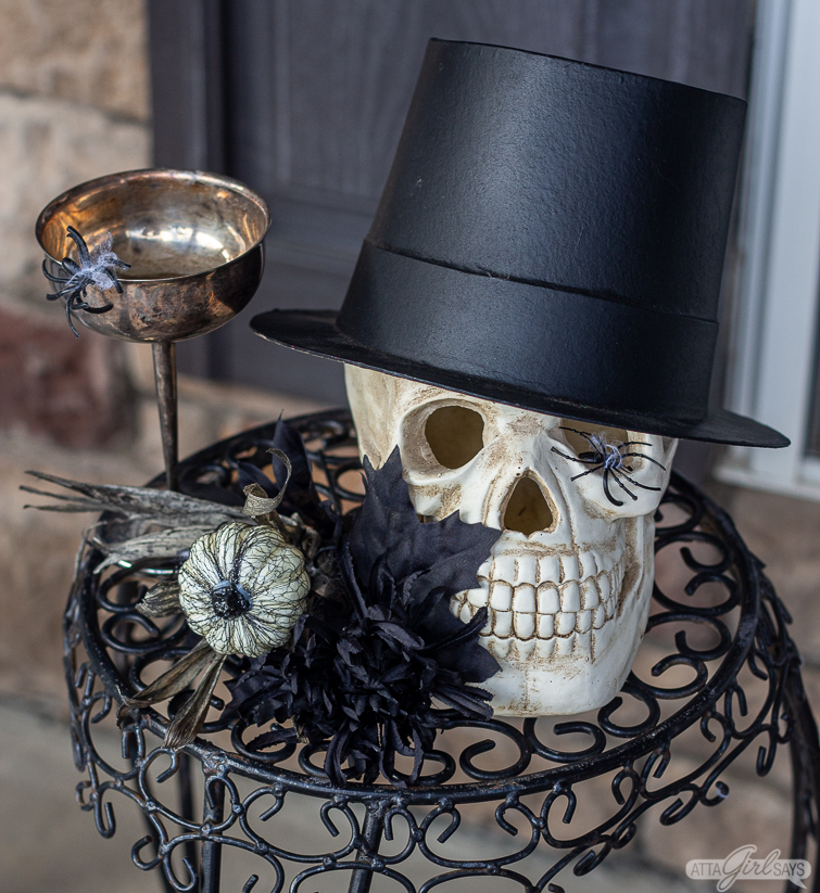 skull wearing a top hat beside a silver champagne coupe