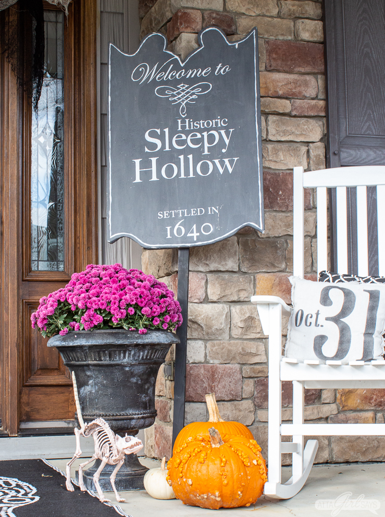 Sleepy Hollow sign, pumpkins and purple mums as front porch Halloween decorations