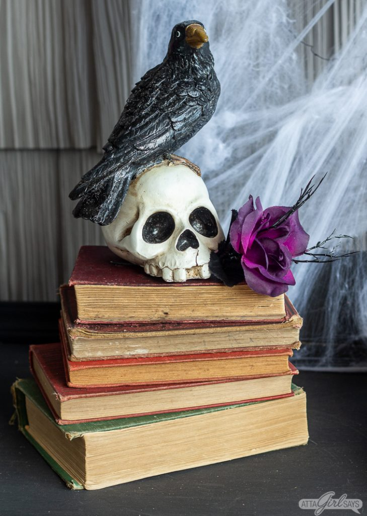 raven sitting on a skull on a stack of old books as part of Halloween front porch decorations