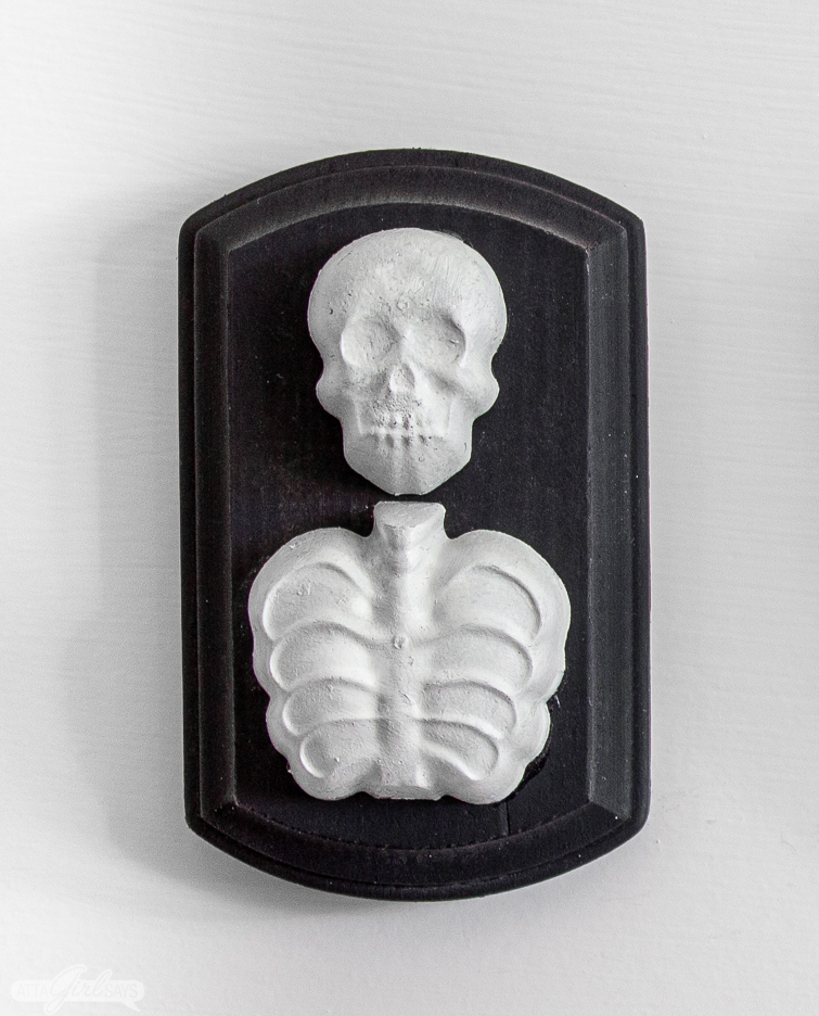 resin skeleton on a black wooden plaque