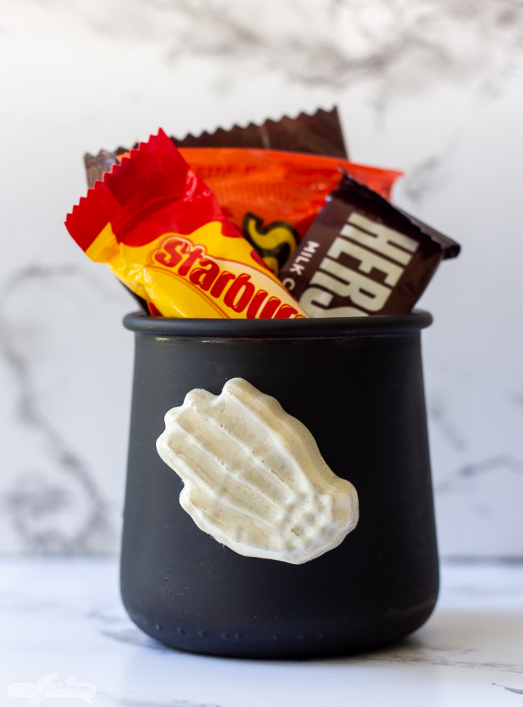 candy-filled Halloween treat jar with a skeleton hand on it