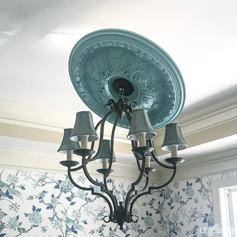 ceiling medallion being installed over a chandelier in a dining room