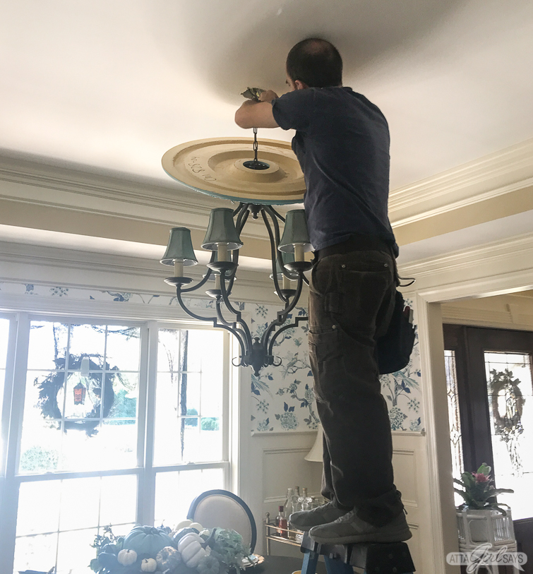 man standing on a ladder installing a ceiling medallion in a dining room