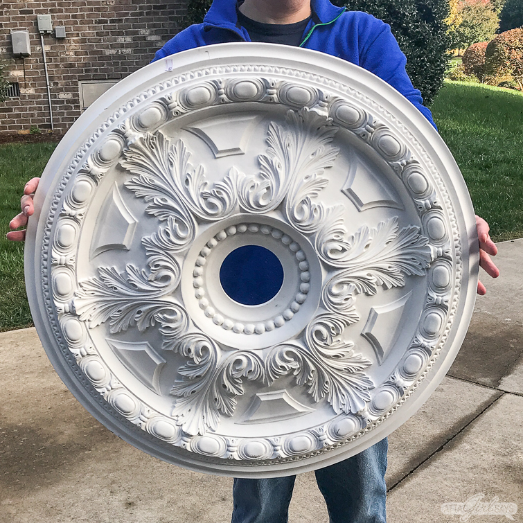 man holding a large unpainted polystyrene ceiling medallion