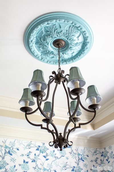 decorative aqua painted ceiling medallion hanging in a dining room with chinoiserie wallpaper