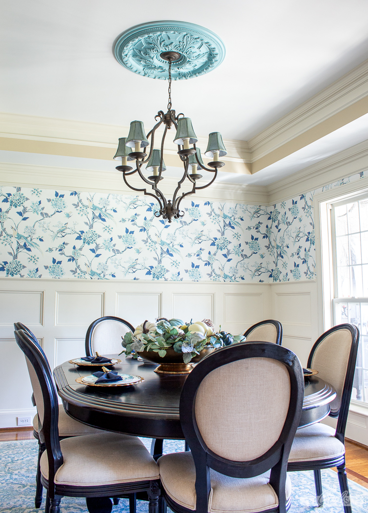 formal dining room with a bird wallpaper and a chandelier with an aqua painted ceiling medallion