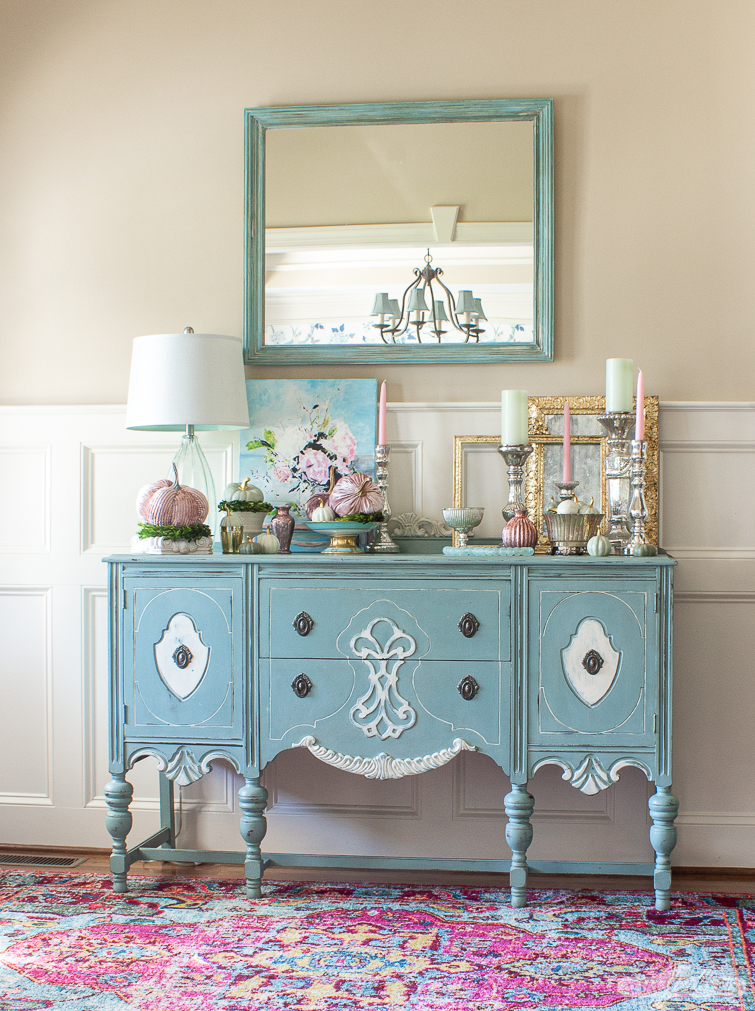 a duck egg blue painted buffet decorated with pastel velvet pumpkins, mercury glass and gilded mirrors for fall