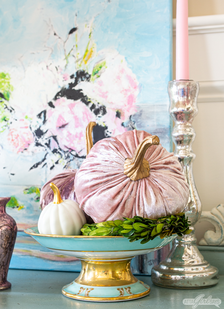 pink velvet and white ceramic pumpkins in an antique blue gilded compote bowl with a peony painting in the background