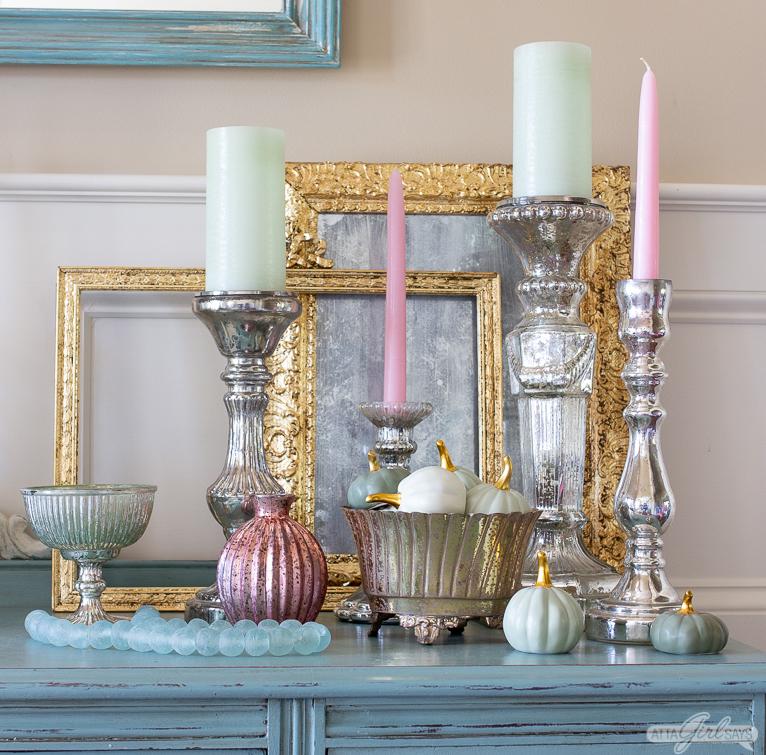 mercury glass candlesticks, seaglass beads, ceramic pumpkins and gilded frames on an aqua blue foyer table