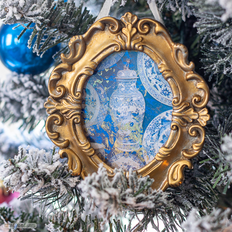 blue and white chinoiserie Christmas ornament in a gilded frames hung on a flocked Christmas tree