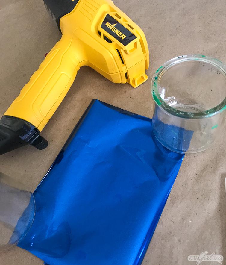 heat gun sitting beside a sheet of blue metallic foil
