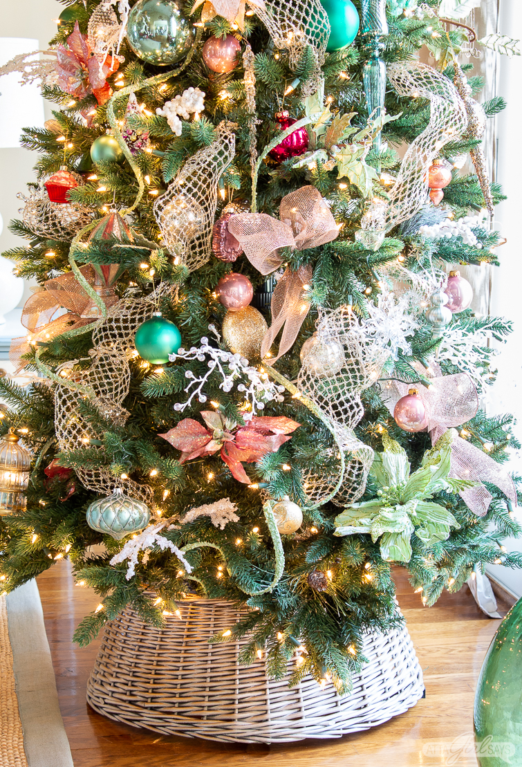 Christmas tree decorated with pink, green and gold ornaments and ribbon