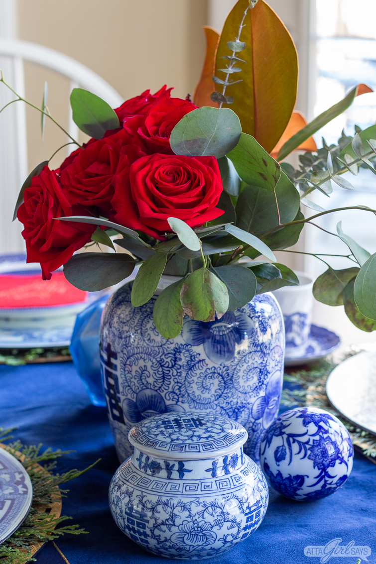 red roses and eucalyptus in blue and white ginger jar for Christmas