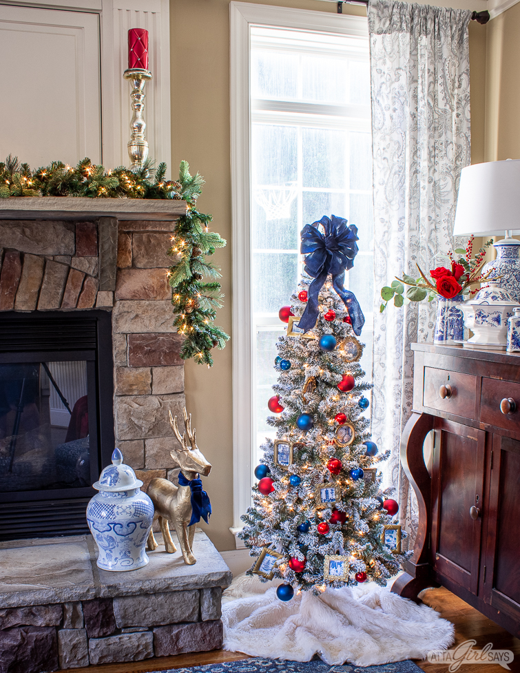 stone fireplace heart with a flocked tree decorated with red and blue and chinoiserie Christmas ornaments