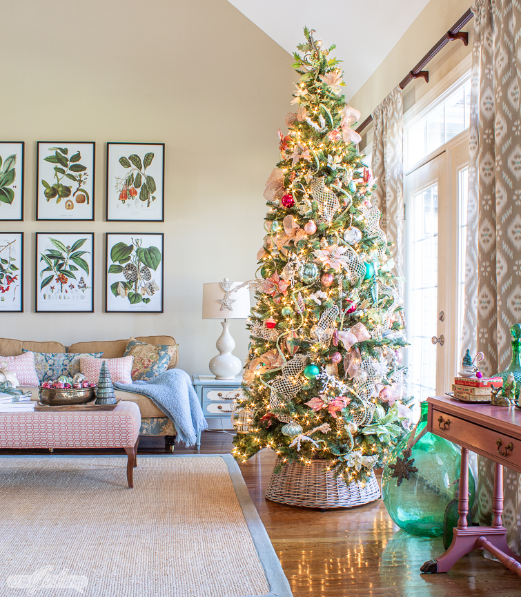 tall skinny Christmas tree with pink and green ornaments in a formal living room decorated in aqua and coral