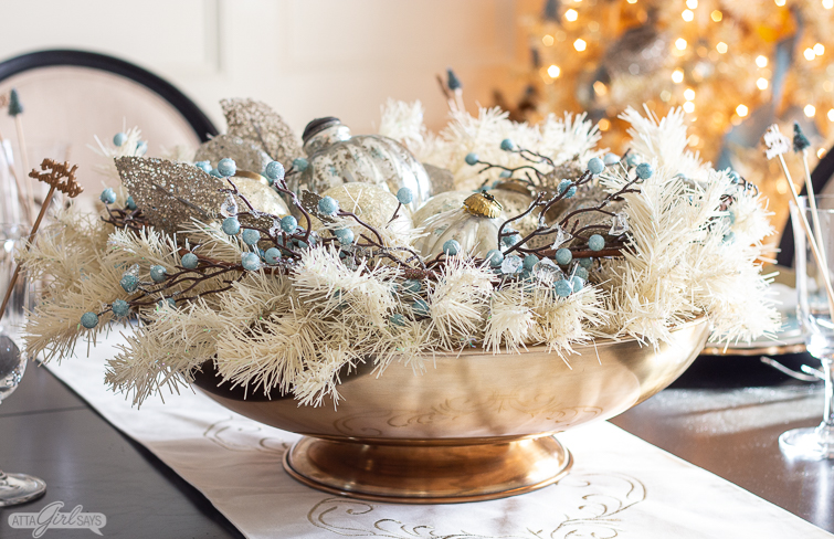 Christmas tablescape centerpiece of ivory garland, blue berries and oversized ornaments in a large gold bowl