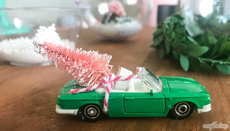 vintage toy green convertible with a pink bottlebrush Christmas tree tied to it