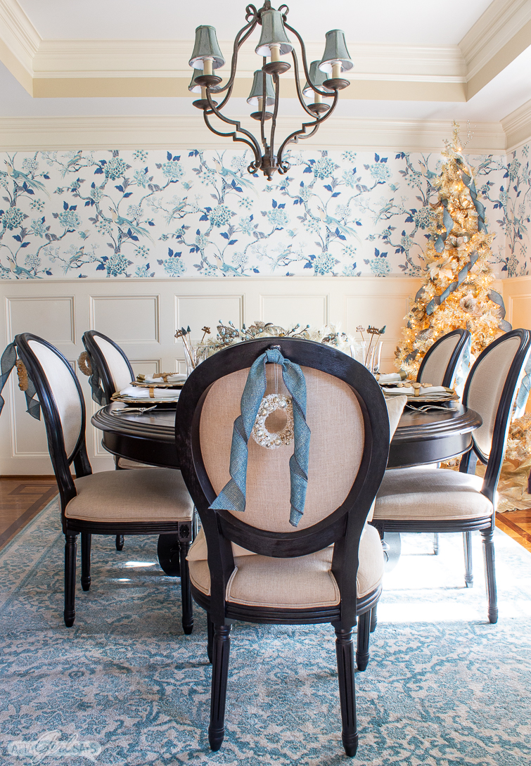 dining room with toile wallpaper, a gold Christmas tree and a formal table set for Christmas dinner
