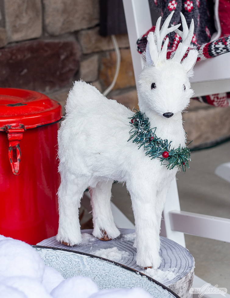 white deer Christmas decoration with a wreath around its neck