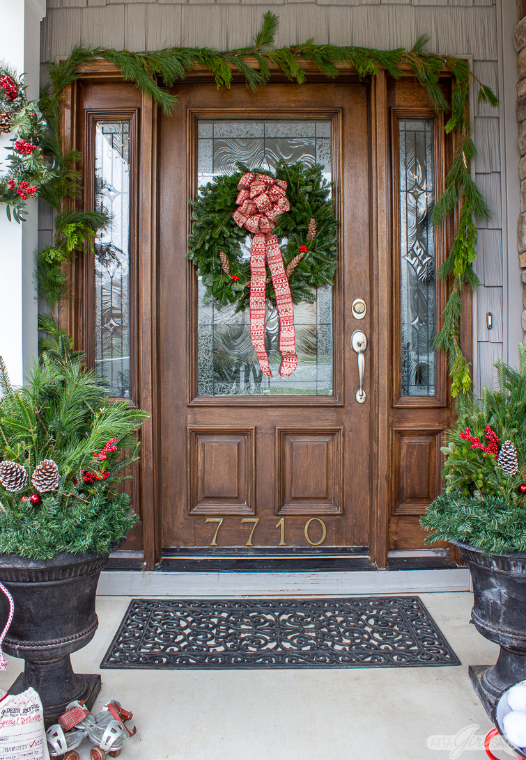 two black urns filled with evergreen arrangements flanking a door with a wreath and fresh garland