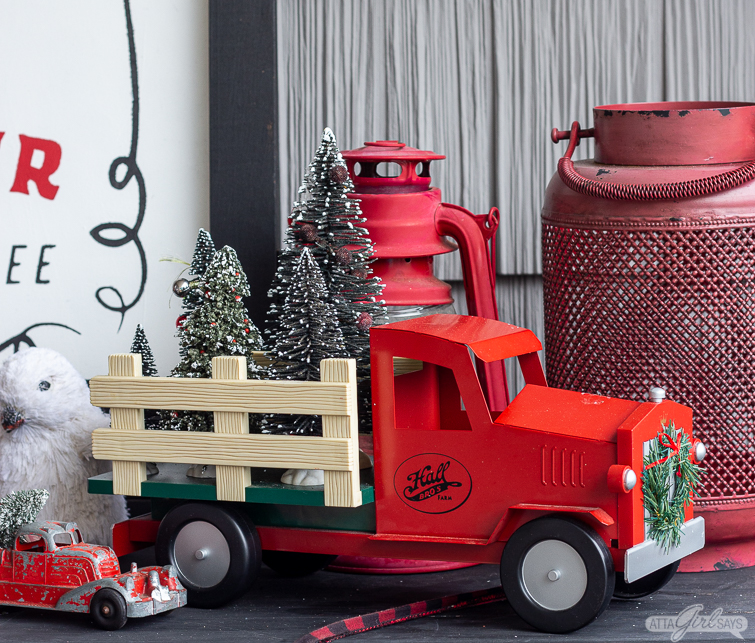 red toy truck with bottle brush trees in the back