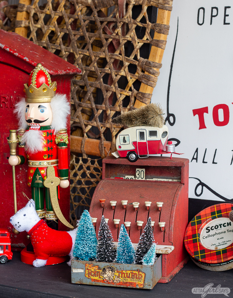 A nutcracker standing beside a child's cash register with bottle brush trees in the drawer as part of a Christmas porch display