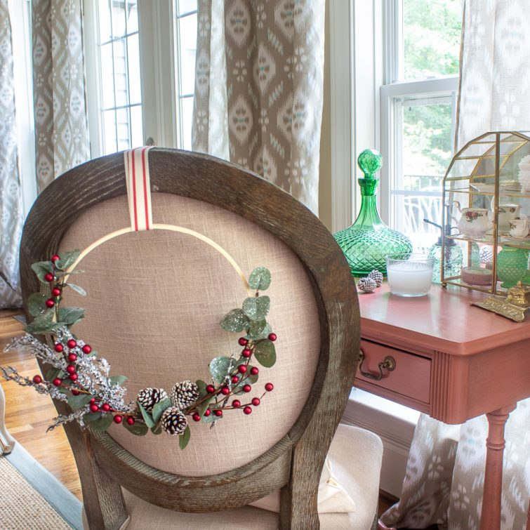 Christmas embroidery hoop wreath hanging on the back of a chair
