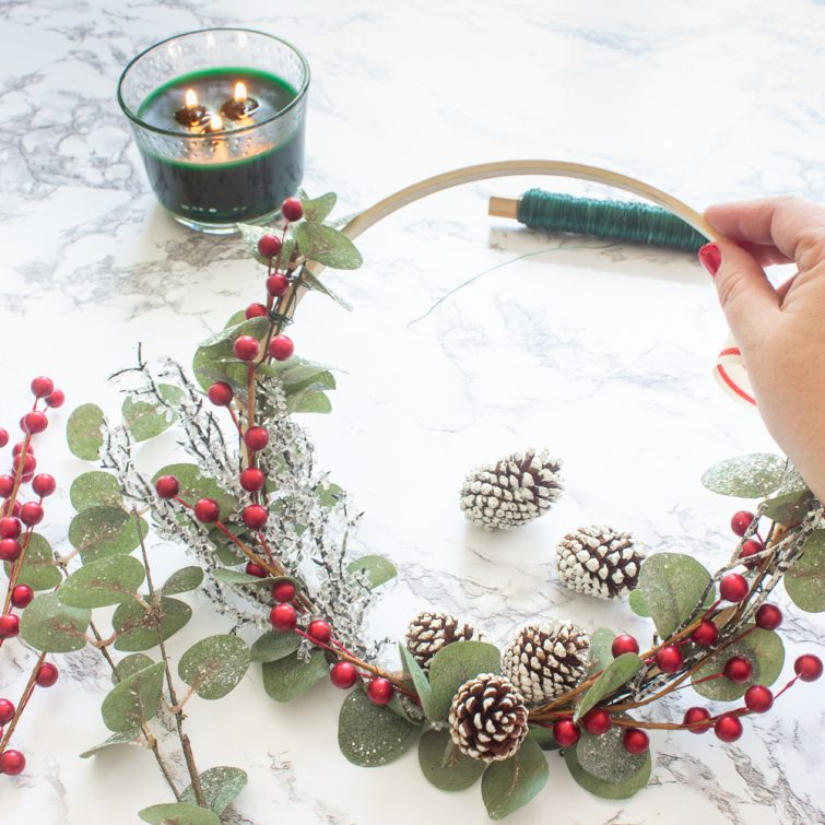 woman's hand holding a Christmas embroidery hoop wreath