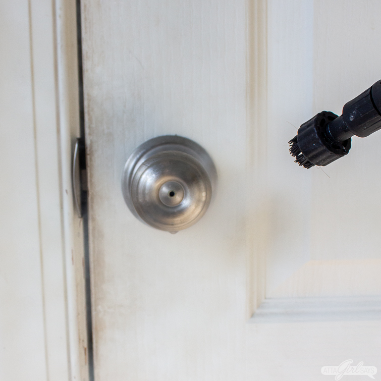 using a steam cleaner to clean a door knob