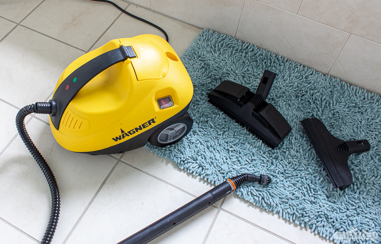 steam cleaner and attachments on a tile bathroom floor