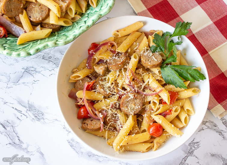 lemon chicken sausage artichoke pasta in a white bowl with tomatoes and parsley