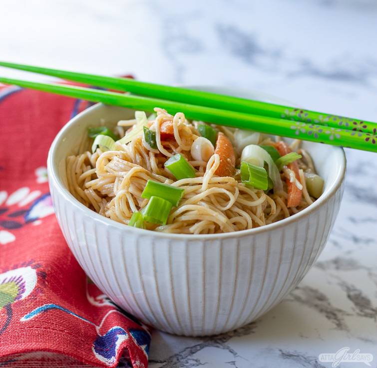vegetarian cold sesame noodles in a bowl with green chopsticks
