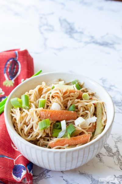 vegetarian cold sesame noodles in a bowl beside a red print napkin