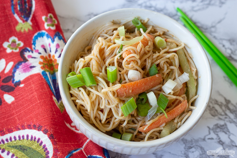 vegetarian cold sesame noodles in a bowl with green chopsticks and a red print napkin