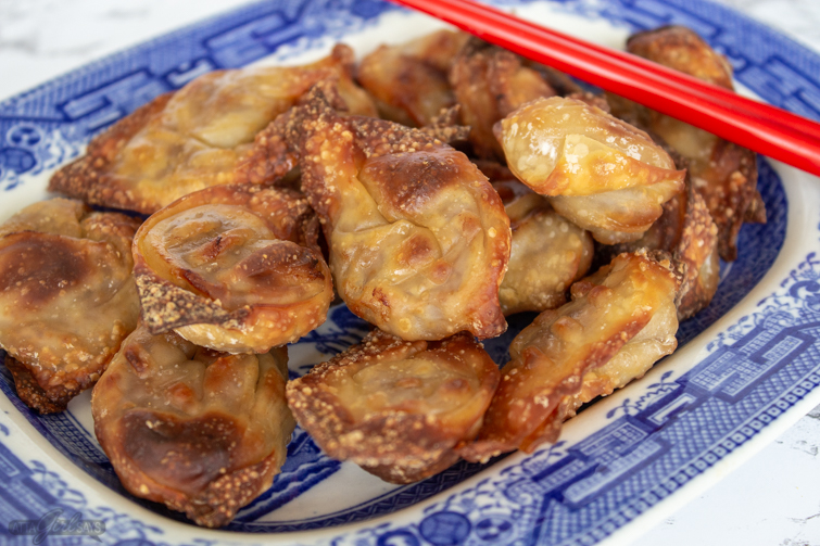 air fryer wontons on a blue and white plate with chopsticks