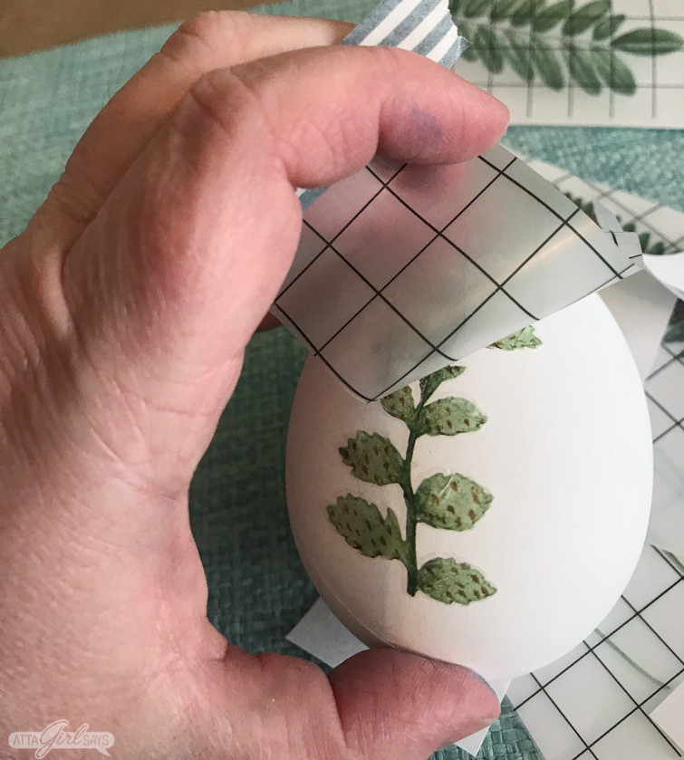 peeling off a decorative rub on transfer to an Easter egg