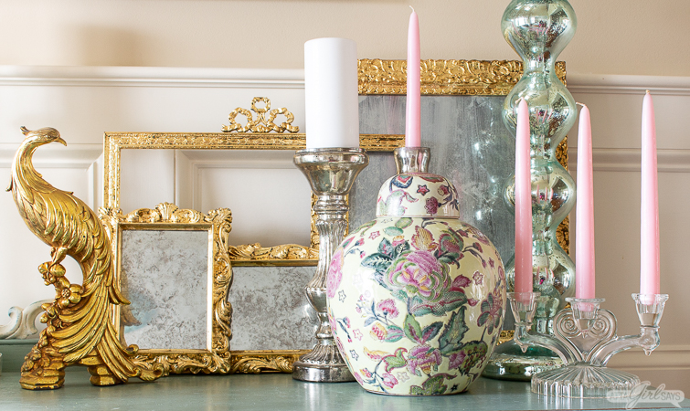 gilded mirrors layered on a painted buffet with mercury glass candlesticks and a ginger jar
