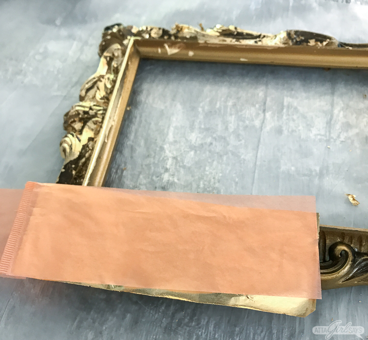 applying gold leaf sheets to an ornate gold mirror