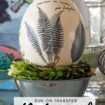 ostrich egg decorated with vintage fern leaf illustrations sitting in a silver bowl
