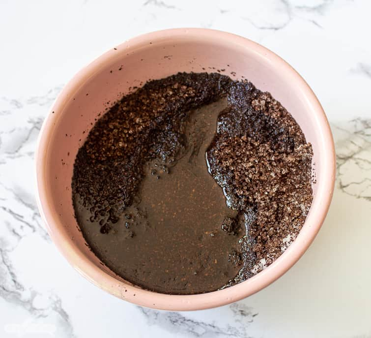 adding coconut oil to coffee grounds and salt for a DIY coffee body scrub