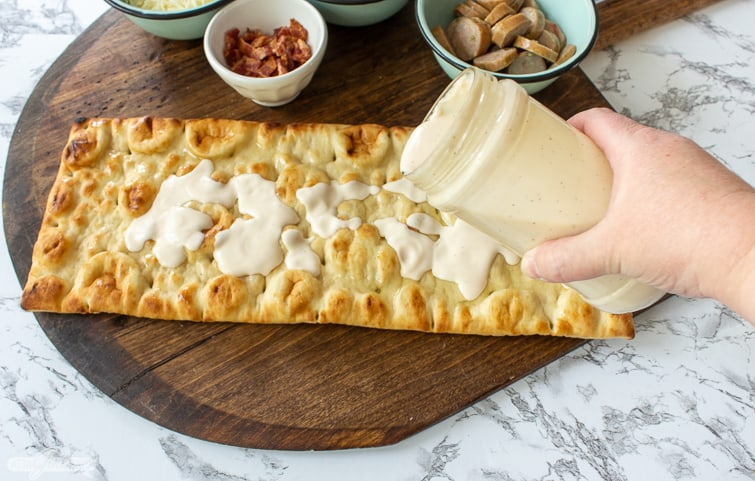 spreading Alfredo sauce on a pizza crust to make chicken bacon artichoke pizza