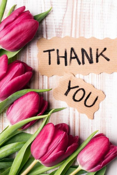 Tulips on a wood background with the words Thank You written on paper