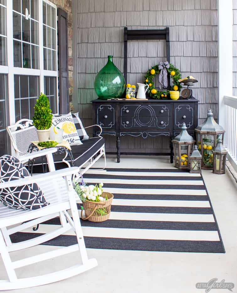 black buffet and white glider bench on a front porch with lemon yellow and green decorative accents