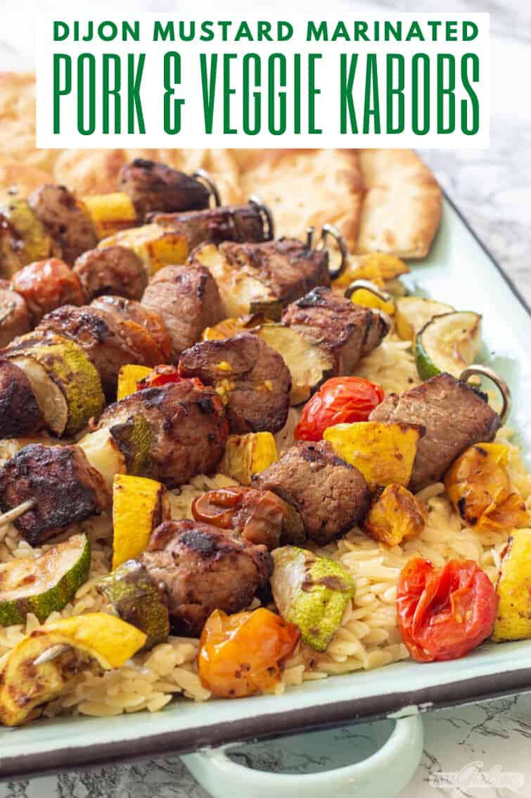platter of pork and vegetable kabobs over orzo